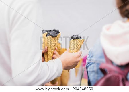 Close-up of Hands of young man with three trendy Delicious fresh charcoal ice cream in waffle cone for himself and for friends. Concept of delicacy, sweets, lifestyle, friendship, summer, heat