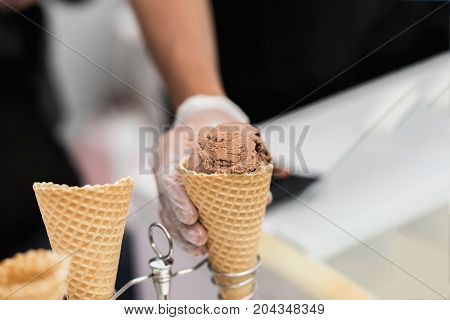Close-up of waffle cone, horn with balls of chocolate, coffee ice cream and hand of seller. Delicious cooling portion for fun. Selective focus. Real scene in store. Copy space, for background