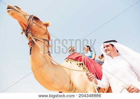 an arabian man and a tourist riding a camel
