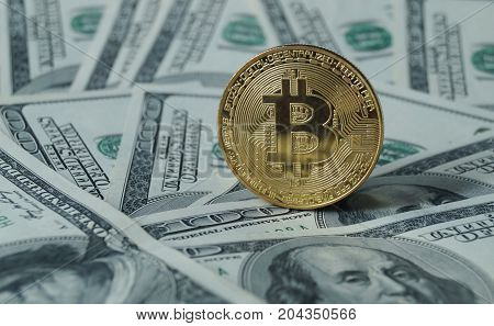 A symbolic coins of bitcoin on banknotes of one hundred dollars. Exchange bitcoin cash for a dollar. Bitcoin invest.