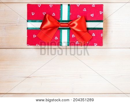 Red gift box on wooden board. Copy space. Holidays concept