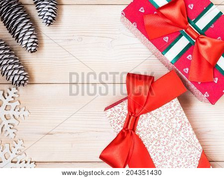 Christmas theme with fir cones along with gift boxes on the wooden background. Top view. Holiday concept