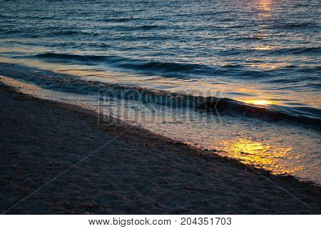 Beautiful sunrise over the sea, orange red sun, purple blue and pink sky without clouds,  blue sea, sunny path, sand wave vacation