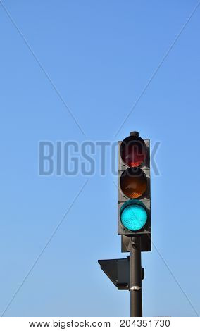 generic traffic signal against a pale blue sky. large copy space
