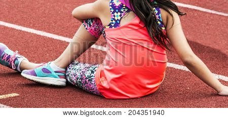 A young women stretches on a red track before track and field practice.