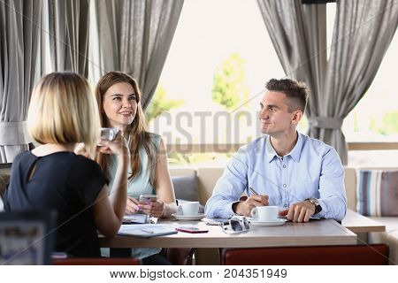 A Group Of People In A Cafe Communicate With A Cup Of Coffee