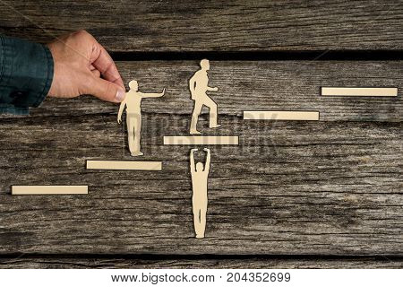 Teamwork concept on rustic wood with group of silhouette cutouts and a male hand helping a paper cutout of a climbing man.