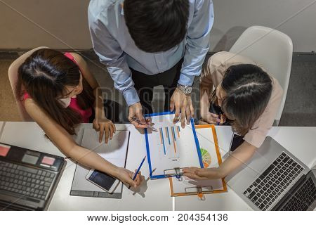 Asian business people discuss about the sales report of company