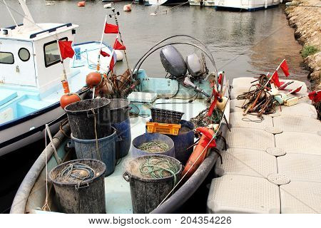 Various ropes boxesbuckets buoys flags and other fishing equipment on a small fishing boat in a harbour