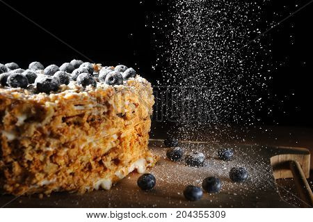 layered cake, Napalion cake, puff cake with blueberry sprinkled with powdered sugar, on a rough wooden backing, menu background