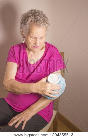 Ice pack on older woman arm to relieve pain