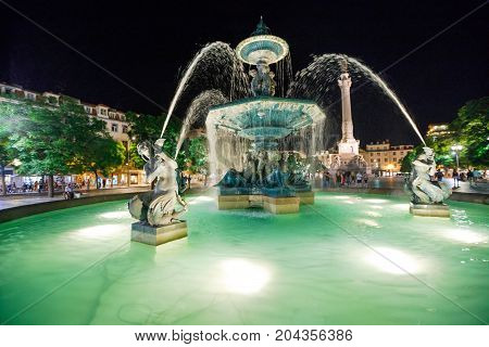 Lisbon, Pombaline District by night. Spectacular baroque fountain illuminated splashing in Rossio Square or Praca Dom Pedro IV in Lisbon, Portugal, Europe. Statue of Dom Pedro IV on the background.