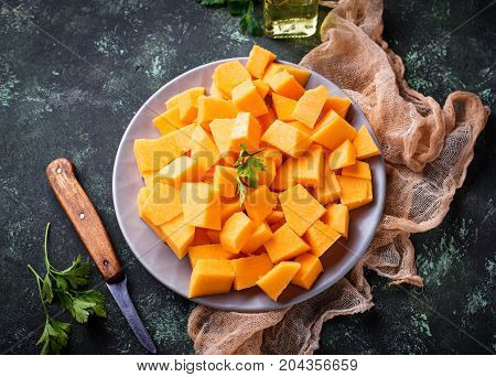 Raw chopped pumpkin on concrete background.  Selective focus