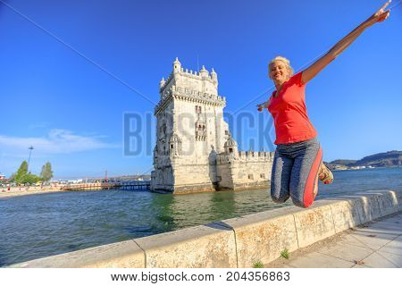 Happy blonde caucasian woman jumping at Belem Tower, Unesco Heritage and symbol of Lisbon, in Belem District, Tagus River. Lifestyle traveler enjoying in Lisbon city. Freedom and travel concept