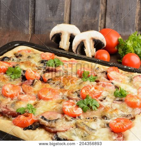 Homemade Pizza With Tomatoes, Mushrooms, Sausage And Cheese Over Wooden Background