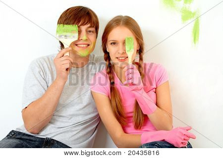 Image of joyful guy and girl hiding one of eyes behind paintbrushes with green color