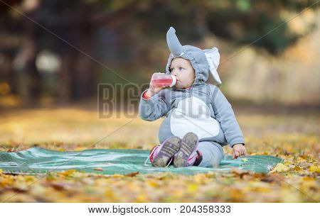 Cute little girl in elephant costume drinking beverage from bottle while playing in autumn forest