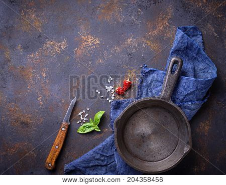 Empty cast iron fried pan with herbs and spices. Culinary background. Top view