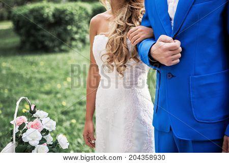 bride holding groom's hand outdoor green backgroud