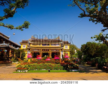HOIAN, VIETNAM, SEPTEMBER, 04 2017: View of an ancient temple with a beautiful jarden with colorful flowers at hoian, in a sunny day in Vietnam.