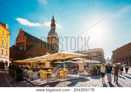 Riga, Latvia - July 1, 2016: People Resting And Walking On Dome Square In Sunny Summer Day. Dome Cathedral On Background Under Blue Sky.