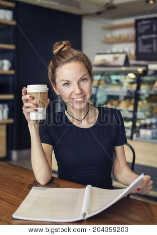 Portrait of a beautiful woman with a copybook and a cup of coffee looking at camera. Student preparing for the exams