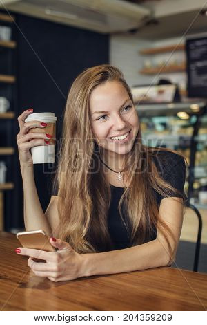 Beautiful young woman drinking coffee with a cellphone in her hand looking at somebody and laughing