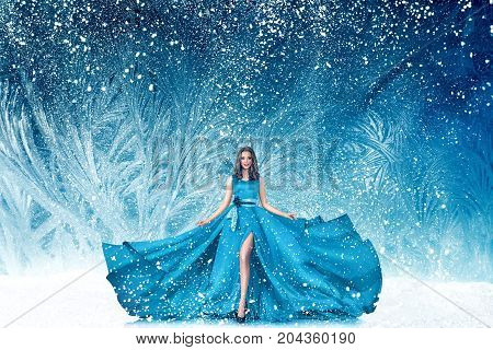 Beautiful young woman in fairy tale forest with long luxurious dress