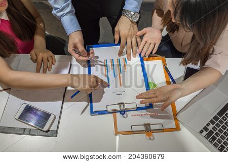 Young business people discuss about sales report in a team