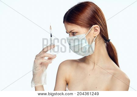 Beautiful young woman on white isolated background holds a syringe, medicine, plastic.