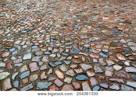 the old roadway of granite cobblestone. Wet road made of stones