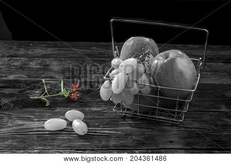 B&W of fruit in a basket and a small flower in color.