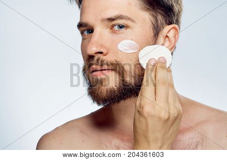 Man with a beard on a light background, cosmetic face cream, cotton pads, portrait.