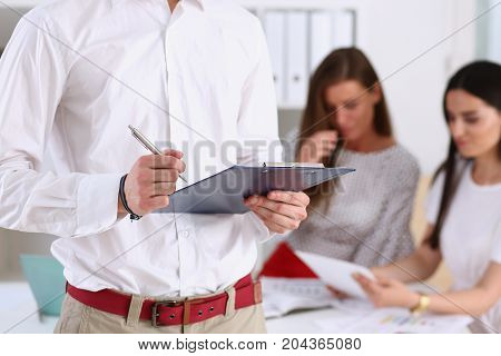 Male arm in office reading and signing employment contract form on clipboard pad with silver pen closeup. Strike a bargain decision white collar motivation corporate sale insurance agent concept