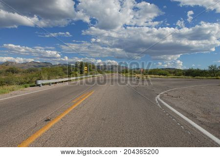 A highway running into the mountains with a split in the road.