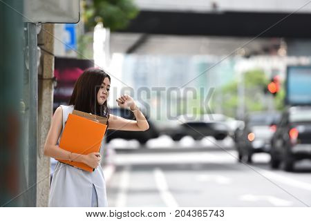 Asian Business woman waiting a cab in a city. Beautiful female is looking to her watch. copy space.