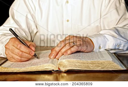 A businessman or business executive in a white long-sleeved shirt takes time out of his day to study the Holy Bible.