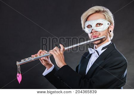 Holidays people and celebration concept. Elegant young guy wearing suit white shirt bow tie and carnival venetian mask playing flute instrument on dark