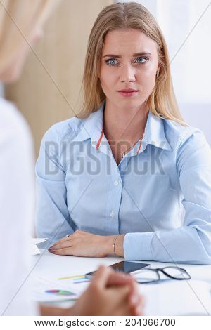 Portrait Of Serious Businesswoman Sitting At Desk