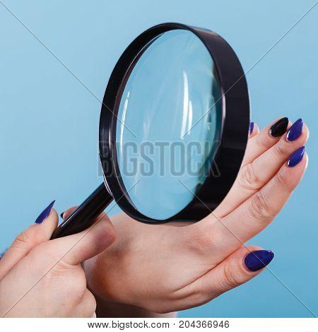 Woman Looking At Nails Through Magnifying Glass