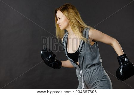 Sportsmanship fairplay and strong body. Young woman fighting boxing. Blonde girl wearing black punch gloves. Sport and fitness power exercising side view on gray