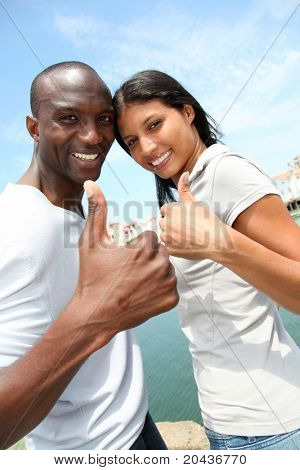 Cheerful couple showing thumbs up
