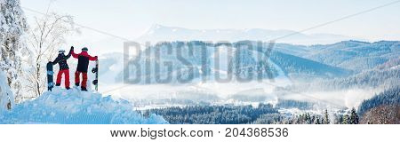 Winter panorama of the Carpathians mountains landscape and forests in a white haze. In the side couple high fiving each other on top of a snowy mountain resting after snowboarding at ski resort