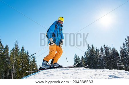 Low Angle And Full Length Shot Of A Skier With Riding Equipment Standing On Top Of The Hill In The M