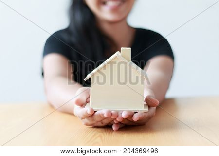 Close up shot female showing the wooden house shallow depth of field select focus on house