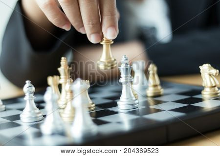Close up shot hand of business woman moving golden chess to defeat a silver king chess on white and black chess board for business challenge competition winner and loser concept selective focus on king chess shallow depth of field