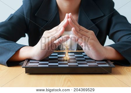 Close up shot hand of business woman protection to the golden chess on white and black chess board for business challenge competition winner and loser concept selective focus on king chess shallow depth of field
