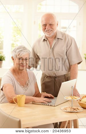 Portrait of senior couple with laptop, woman typing on keyboard, looking at camera, smiling.?