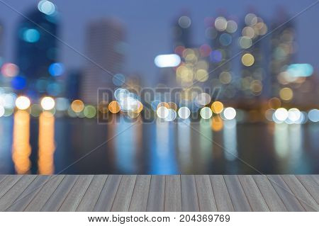 Opening wooden floor City downtown blurred bokeh light night view abstract background with water reflection