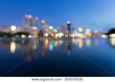 Twilight blurred bokeh light city building with reflection abstract background